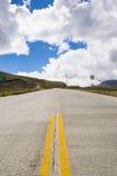 Huvudväg i bergen med en blå himmel Arkivfoton