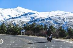 Huvudväg i Spanien till berg Sierra Nevada med sparkcykeln och passagerare royaltyfri foto