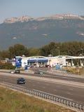 Huvudväg med bensinstationen och berget som bakgrund Royaltyfria Bilder