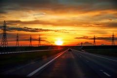 Huvudväg med bilar som reser på solnedgången Arkivbild