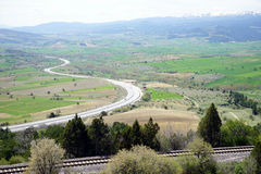 Huvudväg och järnväg nära de snöig bergen Arkivbilder