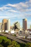 Huvudväg och mer byggnader i affärszon av Bangkok Thailand Arkivfoto
