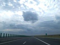 Huvudväg och stormhimmel Arkivfoto