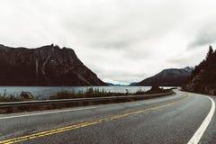 Huvudväg som gränsar sjön i sydliga Argentina royaltyfri bild