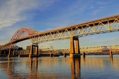 Huvudvägbron och järnvägbron badas i de guld- strålarna av solnedgången Arkivfoton