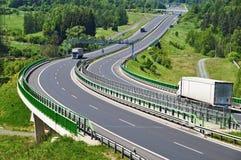 Huvudvägen mellan trän, elektroniska avgiftportar, tre flyttande lastbilar Royaltyfri Bild