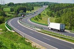 Huvudvägen mellan trän, flyttande lastbilar, elektroniska avgiftportar Royaltyfri Bild