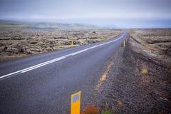 Huvudvägen till och med Island landskap på den dimmiga dagen Arkivfoto