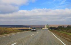 Huvudväglandskap med rörande bilar på dagen Arkivfoto