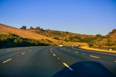 Huvudvägspolning till och med kullar på solnedgången Arkivfoto