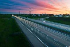 Huvudvägtrafik i solnedgång Arkivfoto