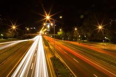 Huvudvägtrafik på natten, lång exponering Arkivfoto