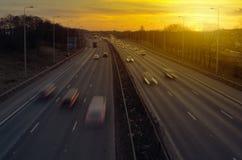Huvudvägtrafik på solnedgången fotografering för bildbyråer