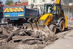 Huvudvägunderhåll, den gula traktoren tar bort gammal asfalt Royaltyfria Bilder