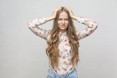 Huvudvärk Den olyckliga blonda flickan som trycker på hennes huvud och, har en migra royaltyfri foto