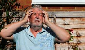 Huvudvärk eller migrän Mannen som rymmer hans huvud smärtar in arkivbilder