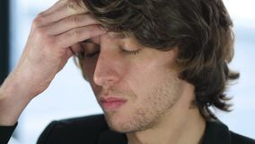 Huvudvärk frustrerad man i hans kontor Arkivbild