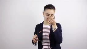 Huvudvärk stressig arbetsöverbelastning för en ung härlig kvinna med exponeringsglas En kvinna tar av hennes exponeringsglas och  stock video