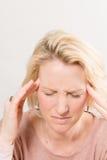 Huvudvärkdam Touches Sides av huvudet med fingerspetsar fotografering för bildbyråer