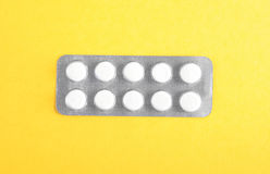 Huvudvärkstablett i en ljus grå packe på en skinande gul bakgrund Prescripted läkarbehandling Sund livsstil Royaltyfri Foto