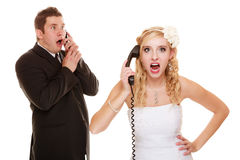 Huwelijk. Boze bruid en bruidegom die op telefoon spreken Royalty-vrije Stock Afbeeldingen