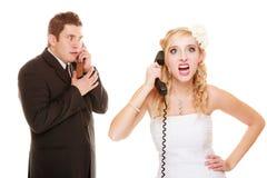 Huwelijk Boze bruid en bruidegom die op telefoon spreken Stock Foto's