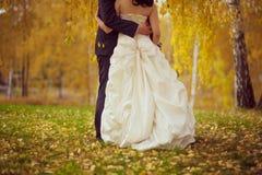 Huwelijk de echtgenoot en de vrouw omhelzen De gouden Herfst Stock Foto's