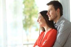 Huwelijk die door een venster thuis kijken Stock Foto's