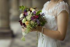 Huwelijk huwelijk handen van de bruid met een huwelijksboeket van bloemen stock foto