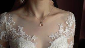 Huwelijk juwelen De bruid in een witte kleding die op een halsband rond haar hals zetten stock footage