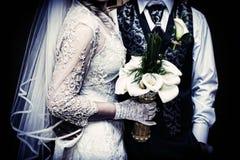 Huwelijkenachtergrond De holdingsbloemen van het huwelijkspaar in handen Stock Foto's