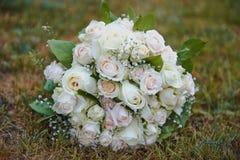 Huwelijks Bruids boeket van roomrozen met baby& x27; s adem om vorm op een grasachtergrond Stock Fotografie