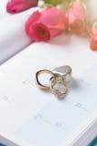 Huwelijks gouden die ringen met slot op kalender worden gesloten Stock Foto's