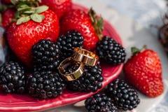 Huwelijks gouden ringen, die ceramische schotels met pruimen, aardbeien, braambessen leggen Bruids juwelendetails en decoratie me Stock Fotografie