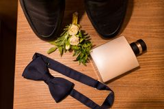 Huwelijks groom's toebehoren Parfum in metaalfles, blauwe bowtie, boutonniere met kleine rozen en een deel van zwarte schoenen Stock Foto