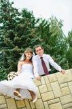 Huwelijks het paar die en bengelt voeten kijken. Tederheid het houden van Royalty-vrije Stock Fotografie