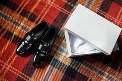 Huwelijks zwarte schoenen en witte doos op de kleurrijke vloer royalty-vrije stock fotografie