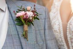 Huwelijksachtergrond, boutonniere op het bruidegomsjasje stock foto