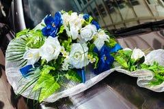 Huwelijksauto met boeketten van witte rozen wordt verfraaid die Stock Afbeeldingen