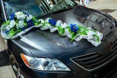 Huwelijksauto met boeketten van witte rozen wordt verfraaid die Royalty-vrije Stock Foto