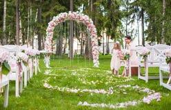 Huwelijksbanken met gasten en bloemboog voor stock fotografie