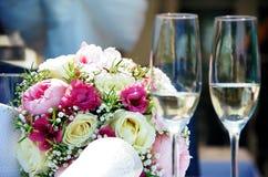 Huwelijksbloemen en alcoholglazen Stock Foto's