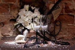 Huwelijksbloemen, ringen en stemware met decoratie Stock Foto