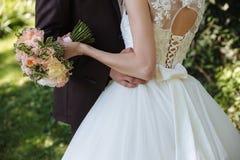 Huwelijksboeket in de handen van het huwelijkspaar Royalty-vrije Stock Foto