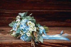 Huwelijksboeket die op een houten oppervlakte liggen stock afbeelding
