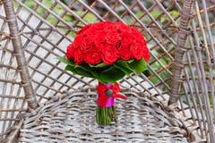 Huwelijksboeket en decoratie rode rozenbloemen op rieten meubilairleunstoel voor Bruidbruidegom Details van weddag Royalty-vrije Stock Afbeeldingen