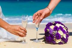 Huwelijksboeket en twee glazen champagne op het zand Mannelijke a Royalty-vrije Stock Afbeeldingen
