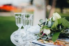 Huwelijksboeket met glazen op de ceremonielijst Stock Afbeelding