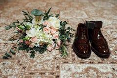 Huwelijksboeket met mensenschoenen Stock Foto