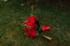 Huwelijksboeket met rode rozen die op een groen gras liggen Royalty-vrije Stock Afbeelding